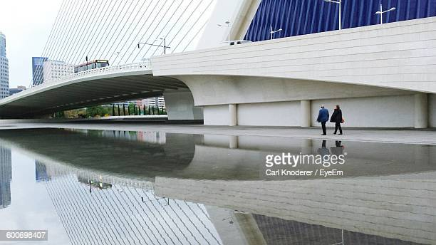 People Walking By Bridge Reflecting In Lake