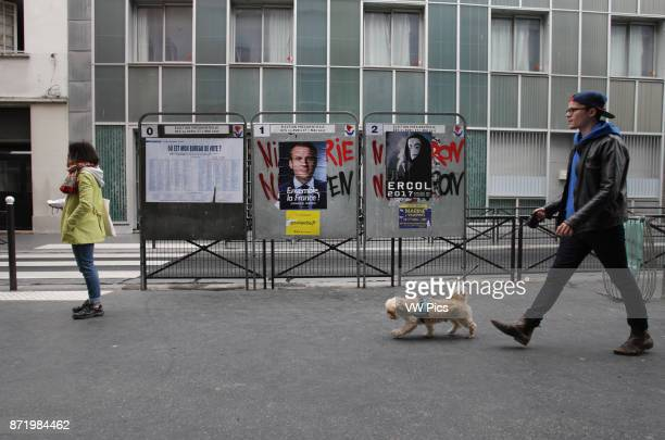 People walking by campaign posters of French presidential candidate Emmanuel Macron of the En Marche movement on the 18th district of Paris as French...