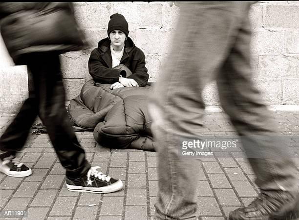 People walking by homless man, sitting on street, (B&W)