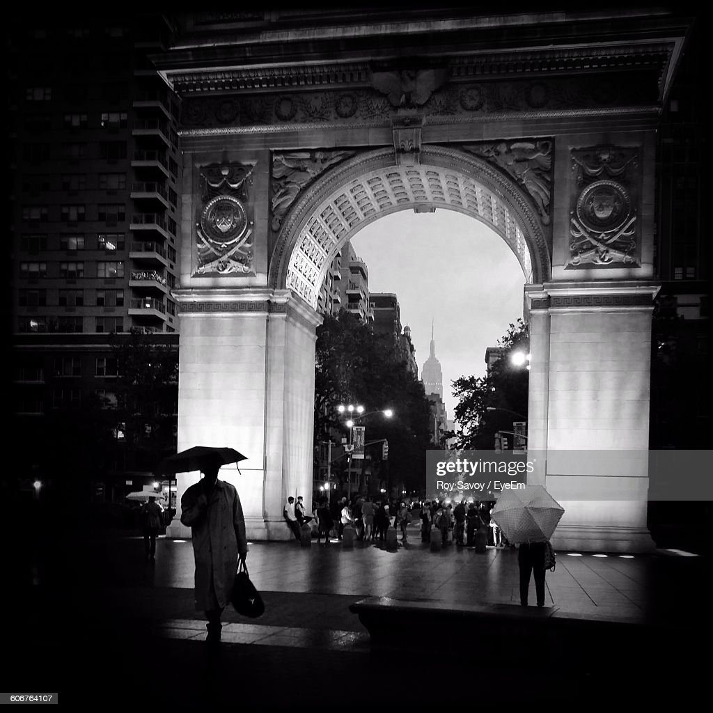People Walking By Illuminated Arch Structure In Washington Square Park At Night