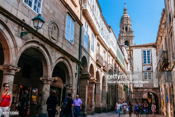People walking down a typical pedestrian cobbled street with archs in old town with the Cathedral of Santiago de Compostela at back