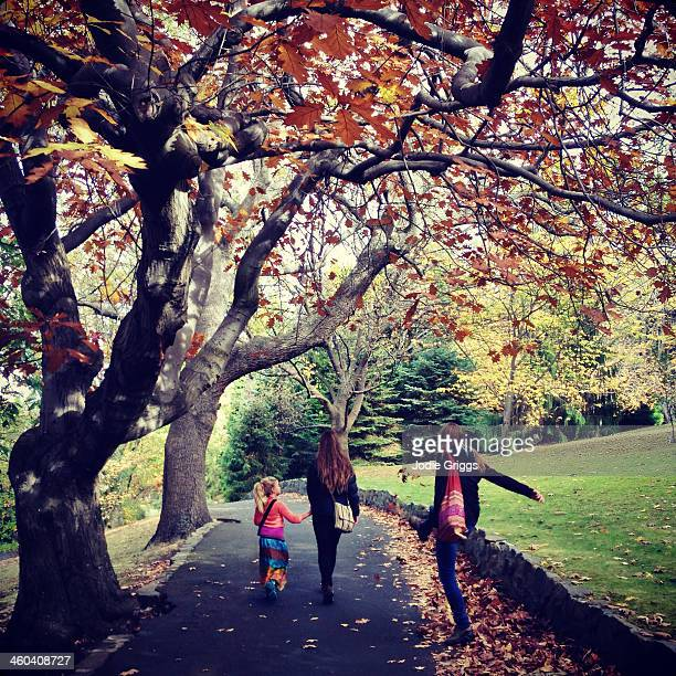 People walking down garden path playing in leaves
