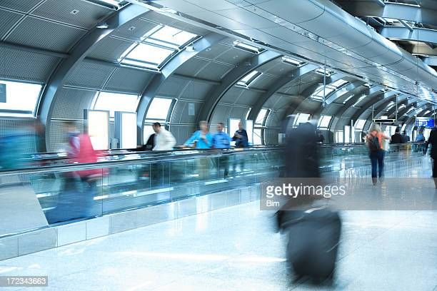 People Walking in Airport Tunnel, Pulling Luggage, Blurred Motion