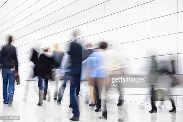 Pessoas a caminhar em corredores, movimento borrado