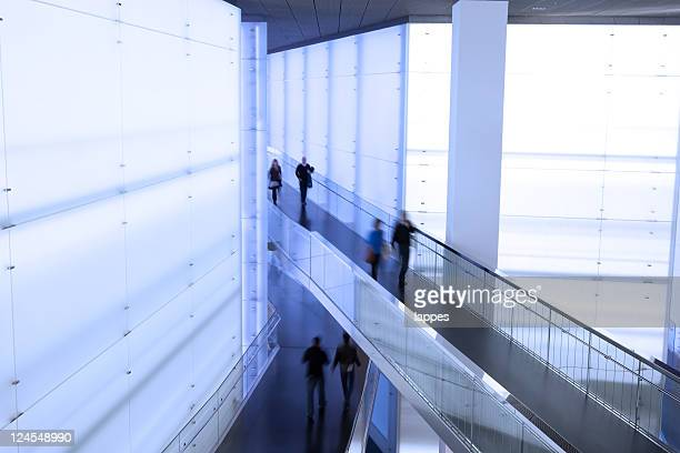 People walking in different direction in commercial building