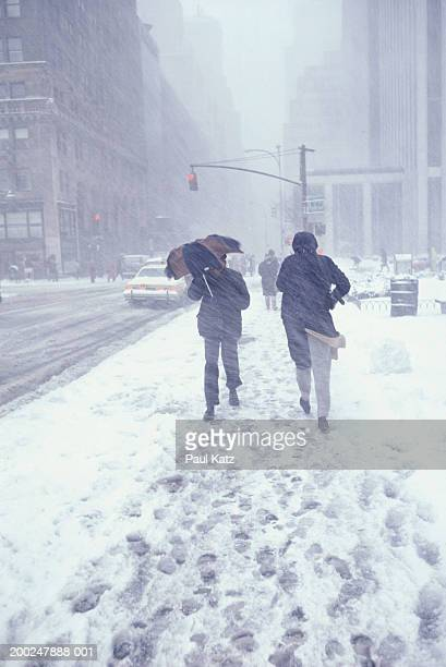 People walking in street in snowstorm, NYC, NY, USA