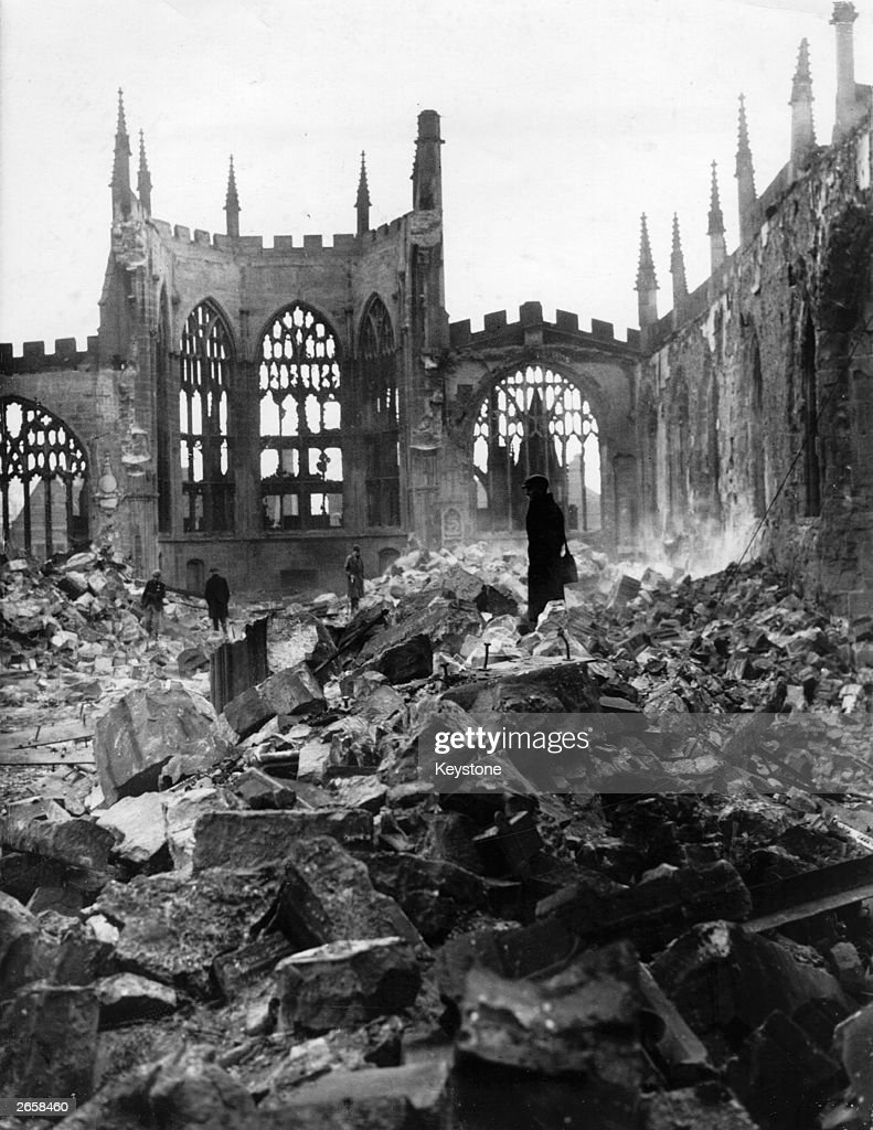People walking in the ruins of Coventry Cathedral destroyed in a heavy German air raid during the Blitz