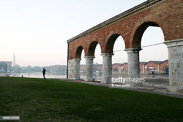 People walking near arches of Venetian Arsenal