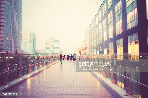 People Walking On Elevated Walkway Amidst City Buildings