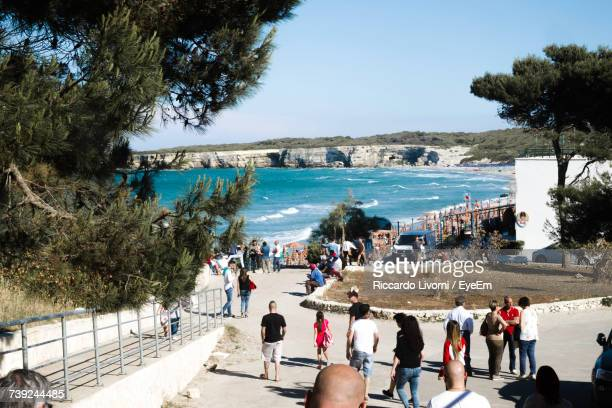 People Walking On Footpath Near Sea During Sunny Day