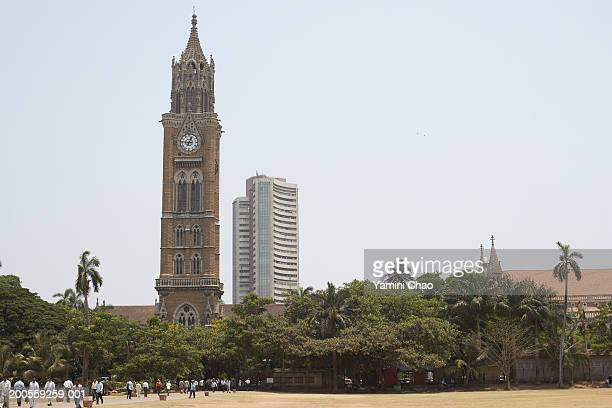 People walking on ground, clock tower and stock exchange in background