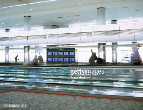 People walking on moving walkway in airport, side view (blurrd motion)