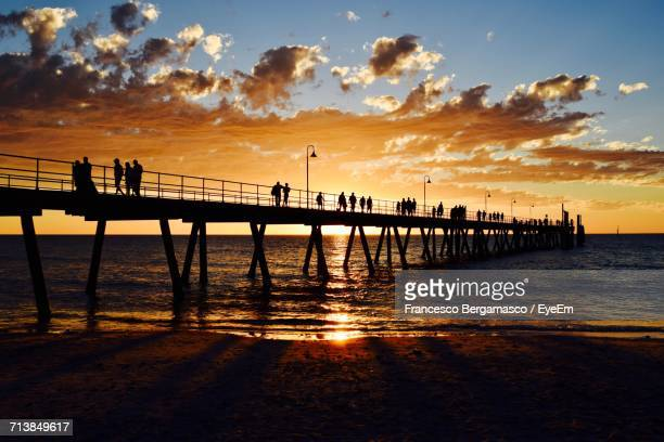 People Walking On Pier Against Sky During Sunset