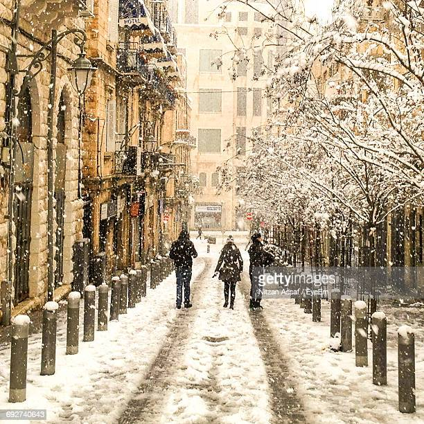 People Walking On Snow Covered City
