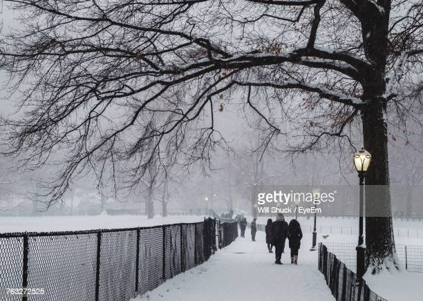 People Walking On Snow Covered Footpath During Winter