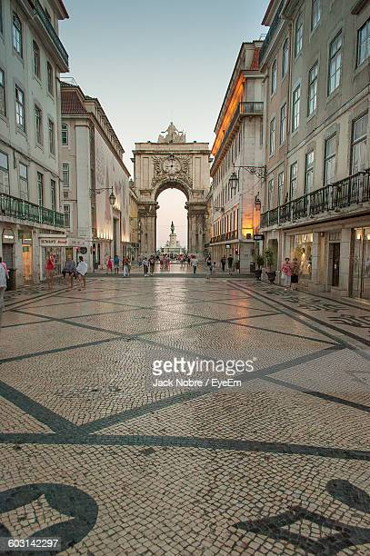 People Walking On Street Amidst Buildings At Praca Do Comercio