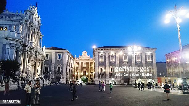 People Walking On Street By Buildings At Piazza Del Duomo Against Clear Sky