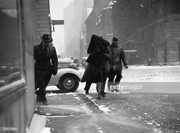 People walking on street in wind, (B&W)