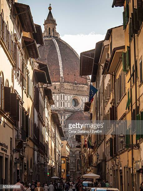 People Walking On Street Leading Towards Florence Cathedral Against Sky