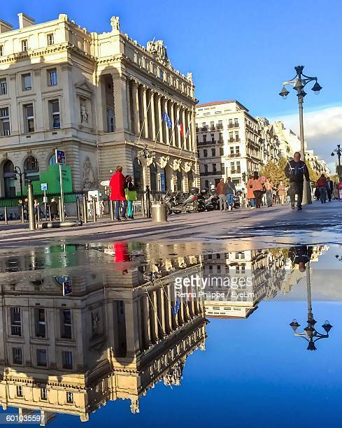 People Walking On Street With Reflection In Puddle