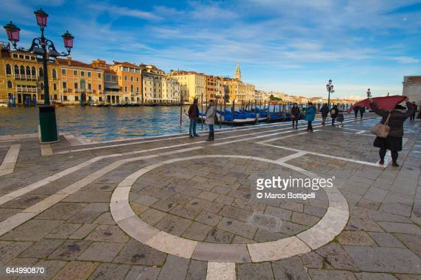 People walking on the banks of the Gran Canal. Venice, Italy.
