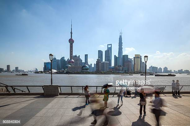 People walking on the Bund promenade in a sunny day, Shanghai, China