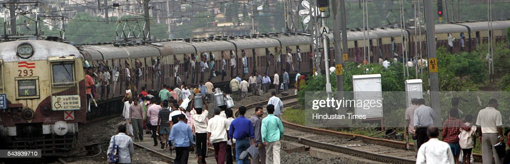 People walking on the railway tracks as locals were stranded in between Mumbra and Diva because the engine of a mail train failed on July 30, 2005 in Maharashtra, India.