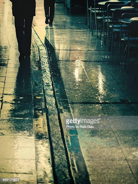 People walking on wet sidewalk
