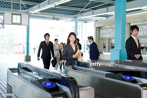 People walking through automatic ticket wicket at station