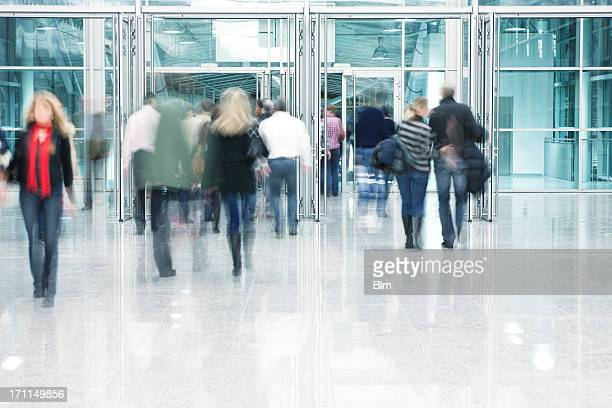 People Walking Through Entrance Door in Modern Building, Blurred Motion