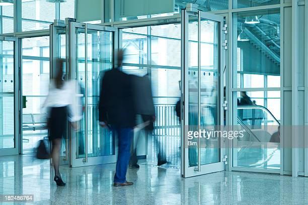 人々徒歩でのエントランスドアのモダンなビル、アクションショット