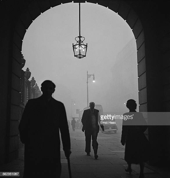 People walking through fog on Piccadilly London circa 1953