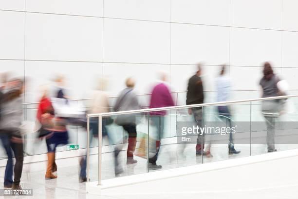Menschen gehen durch die weiße Flur