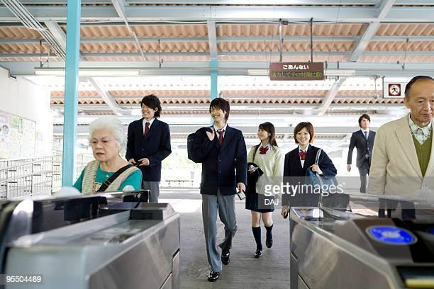 People walking through turnstiles at station