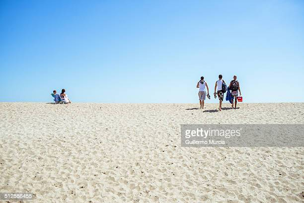 People walking up and seating atop the dune at Rockaway Beach in Queens New York August 24 2014