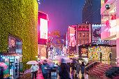 SEOUL, SOUTH KOREA - NOVEMBER 26, 2017 : People walking with umbrellas on a rainy day at  Myeong-dong shopping street at night, Seoul, South Korea