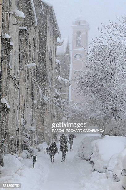 People walks along the streets covered by snow in Corte on January 17 2017 on the French Mediterranean island of Corsica / AFP / PASCAL...