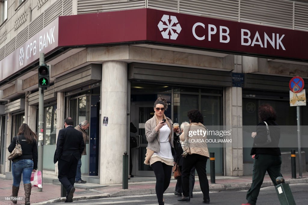 People walks in front of a Cypriot popular bank branch in Athens on March 27, 2013, as Greek subsidiaries of three Cypriot banks reopened today after Greece's third lender, Piraeus bank, signed an agreement to acquire all their deposits, loans and branches. But banks in Cyprus itself remained closed as authorities worked out a plan to get them back up and running amid the country's financial crisis.
