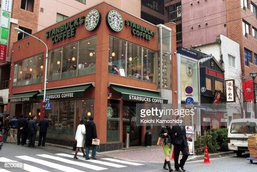People walks in front of a Starbucks Coffee shop March 17 2001 in Tokyo Japan Since opening its first store in Japan in August 1996 Starbucks has...