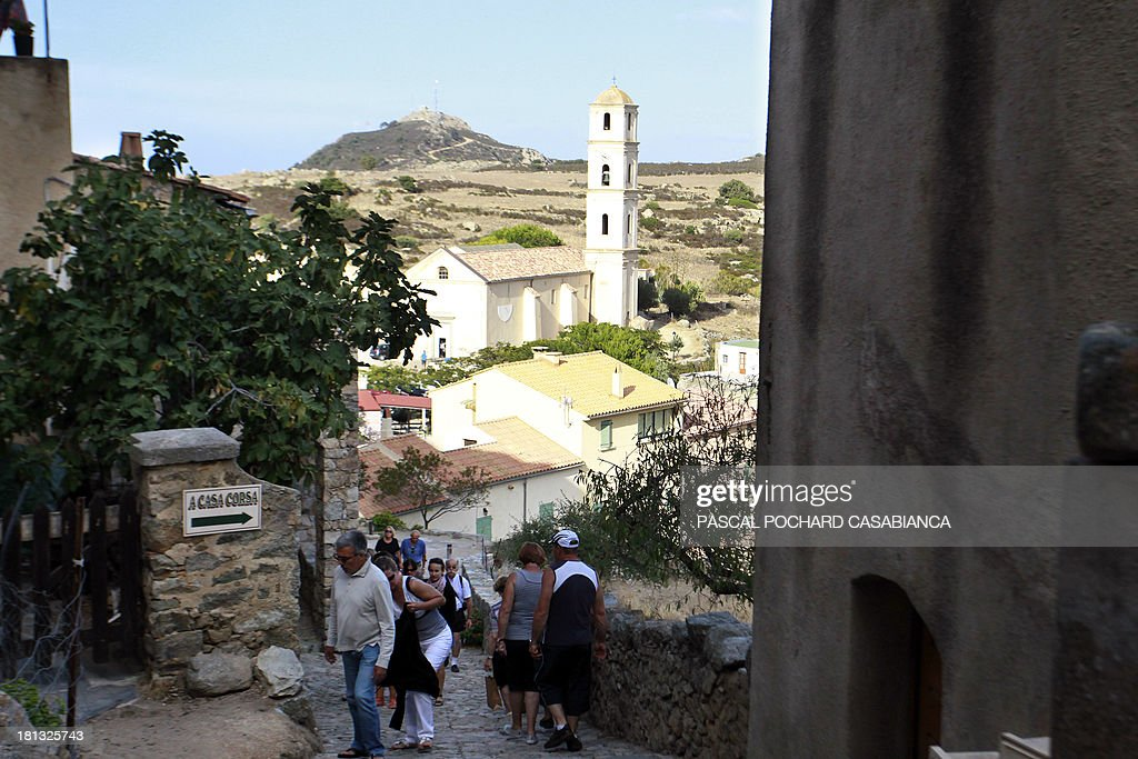 People walks, on September 19, 2013, in a street of the village of San Antonino village on the French Mediterranean island of Corsica. San Antonino is listed as one of the most beautiful villages of France. AFP PHOTO / PASCAL POCHARD-CASABIANCA