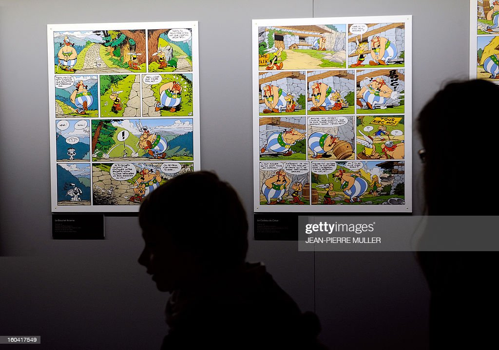 People walks past Asterix comics boards, on January 31, 2013 on the opening day of the 40th edition of the Angouleme International Comics Festival in Angouleme, southwestern France, as part of a tribute to Albert Uderzo, French author and illustrator who launched the Asterix comics strip character in 1959 with author Rene Goscinny. AFP PHOTO / JEAN-PIERRE MULLER