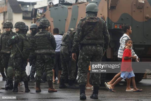 People walks past Brazilian soldiers during a 'Mega Operation' conducted by the Brazilian Armed Forces along with police against gang members in...