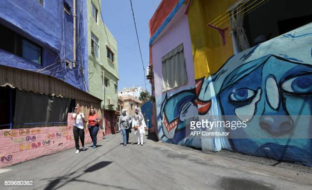 People walks past houses painted as part of the 'Ouzville' project in Beirut's southern Ouzai neighbourhood on August 19 2017 Starting 18 months ago...