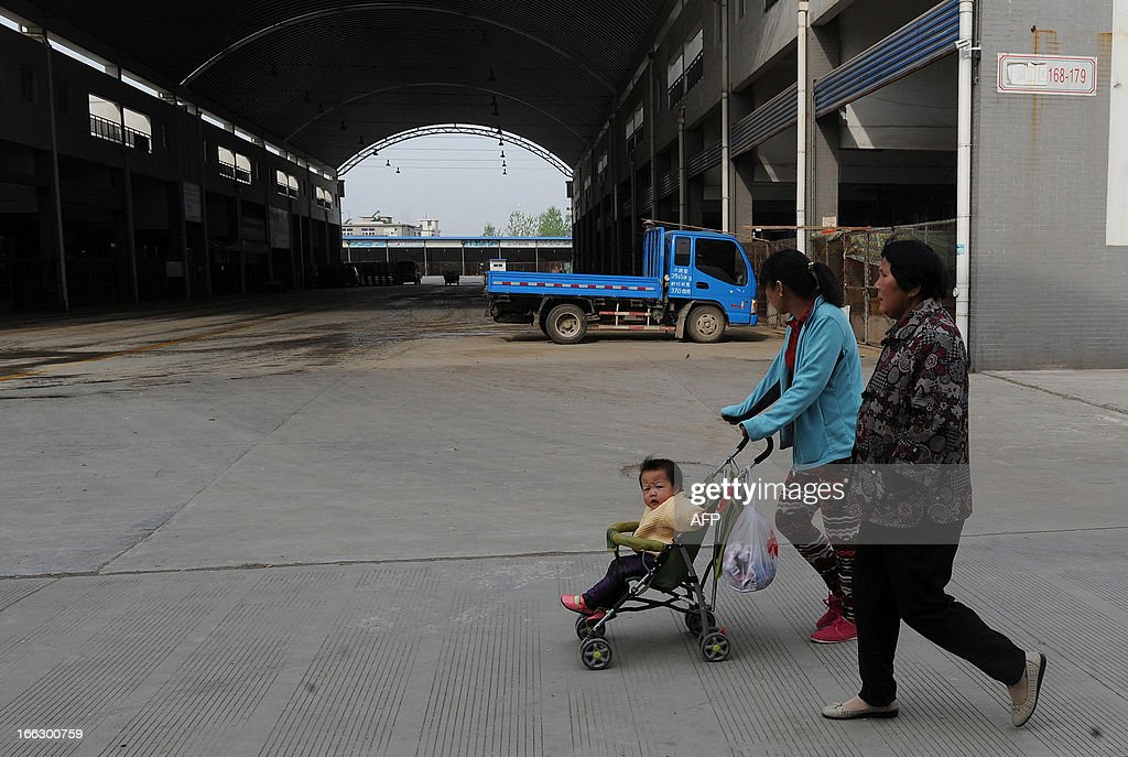 People walks past the closed Huishang Wholesale Poultry Market after positive samples of H7N9 were found at the market in Hefei, central China's Anhui province on April 11, 2013. The number of cases of the H7N9 strain of avian influenza rose to 33 on April 10, with nine deaths since China announced over a week ago that it had been found in humans for the first time. CHINA