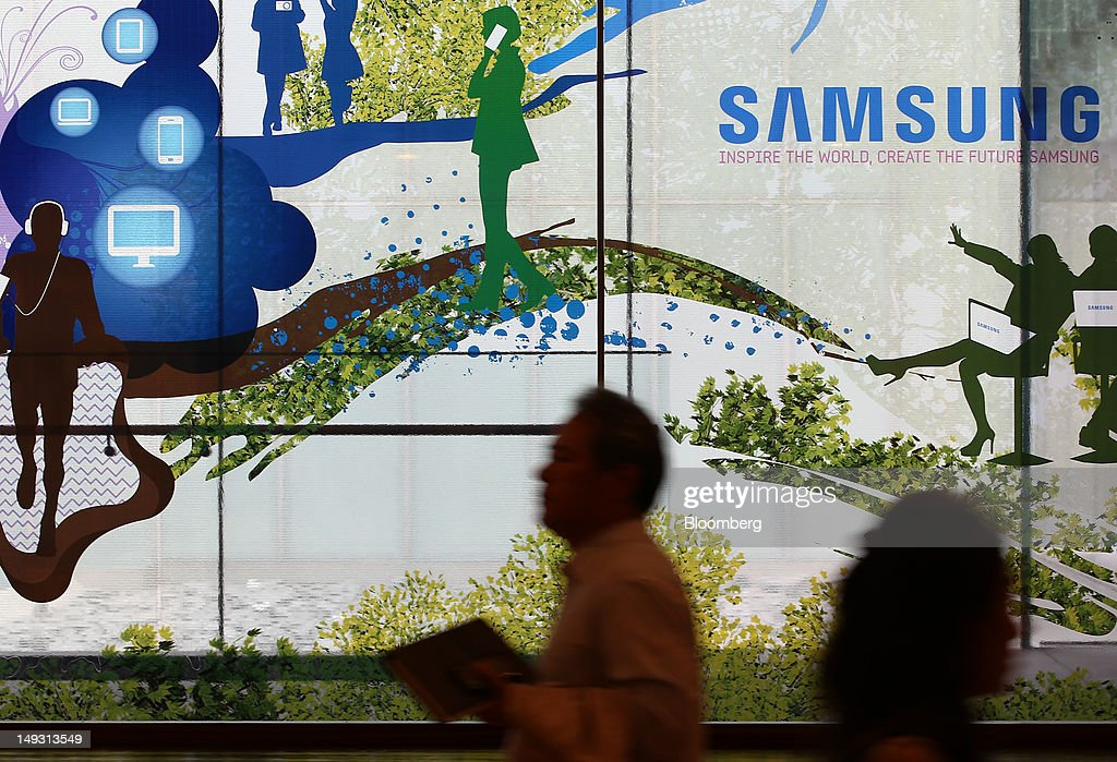 People walks past the Samsung Electronics Co. logo displayed at the company's Seocho offices in Seoul, South Korea, on Thursday, July 26, 2012. Samsung, the world's largest maker of TVs and mobile phones, reported second-quarter profit that missed analysts' estimates after chip prices weakened and smartphone output failed to keep up with demand. Photographer: SeongJoon Cho/Bloomberg via Getty Images