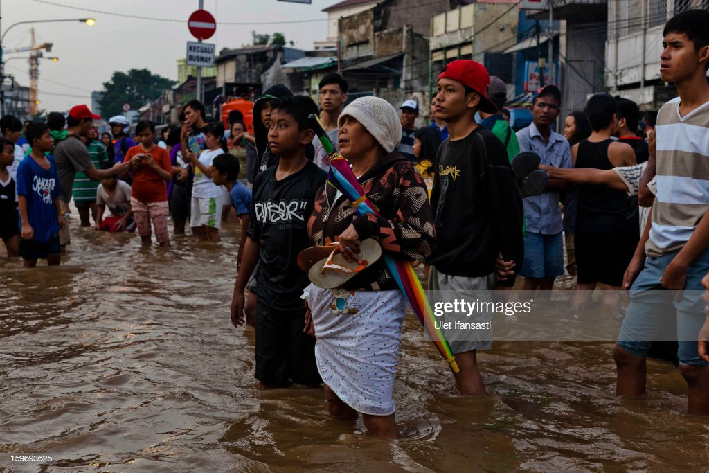 People walks through floodwaters as the Ciliwung River overflows in East Jakarta district on January 18, 2013 in Jakarta, Indonesia. According to the National Disaster Management Agency, about 50 percent of the capital is under water following the floods which have so far claimed eleven lives and displaced thousands of Indonesians.