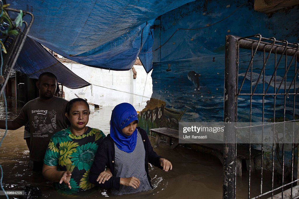 People walks through floodwaters in Central Jakarta district on January 18, 2013 in Jakarta, Indonesia. According to the National Disaster Management Agency, about 50 percent of the capital is under water following the floods which have so far claimed eleven lives and displaced thousands of Indonesians.