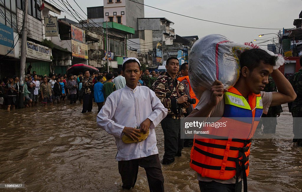 People walks through floodwaters in East Jakarta district on January 18, 2013 in Jakarta, Indonesia. According to the National Disaster Management Agency, about 50 percent of the capital is under water following the floods which have so far claimed eleven lives and displaced thousands of Indonesians.