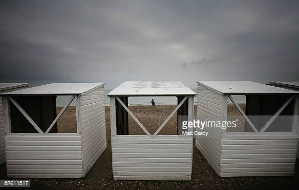 People wall past empty beach huts at Weymouth seafront on August 31 2008 in Weymouth England Forecasters have claimed that this August has been one...