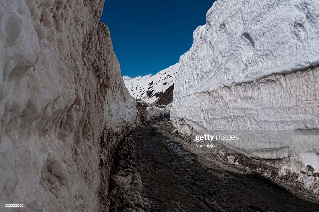 people wall through the through the snow cleared Srinagar-Leh highway in Zojila, 108 km (67 miles) east of Srinagar, the summer capital of Indian controlled Kashmir, India. on April 30, 2016. The 443 km (275 mile) long highway was opened for the season by Indian Army authorities after the remaining snow at Zojila Pass, some 3,530 metres (11,581 feet) above sea level, had been cleared. The pass connects Kashmir with the Buddhist-dominated Ladakh region, a famous tourist destination known for its monasteries, landscapes and mountains.